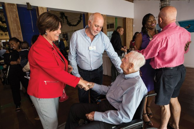 From left: With his wife, Esther, Rassin mingles with fellow members of the Rotary Club of East Nassau.