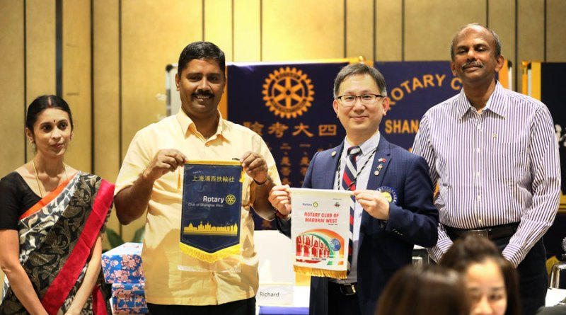 Club Presidents Evan Huang and SB Rajkumar exchange flags. Sumathi Rajkumar and Past President MS Sundaravel are also in the picture.