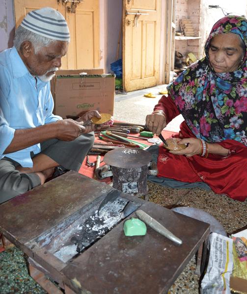 Craftsmen at work making a lac bangle.