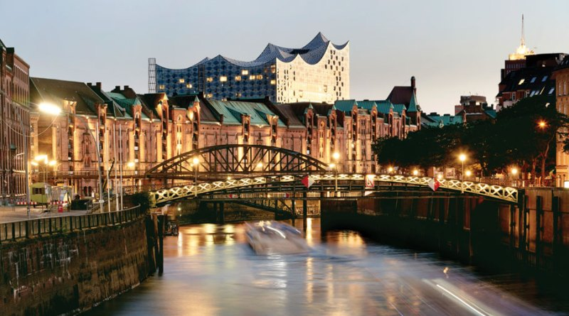 The wavy roofline of Hamburg's newest landmark, the Elbphilharmonie, breaks above the historic brick warehouses of the Speicherstadt district.