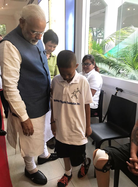 Prime Minister Narendra Modi with a beneficiary at a camp organised by the club in Manila.
