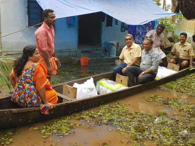 Rotarians ride on a boat to distribute relief material to flood victims.