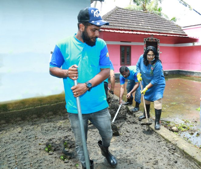 Volunteers led by Rtn Tina Antony (right) clean houses after the floods.