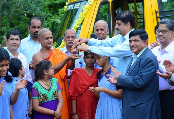 DG Abhinandan Shetty handing over the keys of the bus to Vishwasprasanna Theertha Swamiji, Chairman, Vishwajaneena Trust. IPDG G N Prakash is also present.