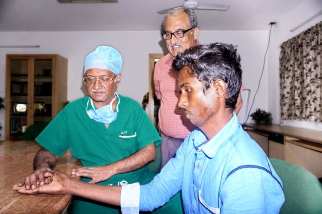 Dr Rajasabapathy evaluating a prospective patient for reconstructive surgery as RCCM President K K Chugh looks on.