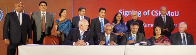 PDG J B Kamdar and Sanjay Parmar, TRF Manager, RISAO, sign the CSR MoU as RI President Barry Rassin looks on. Also seen: (seated) Marlene Kamdar, TRF Trustee Mike Webb; (standing) RID C Basker, DG Babu Peram, TRF Trustee Gulam Vahanvaty and PRIP K R Ravindran.