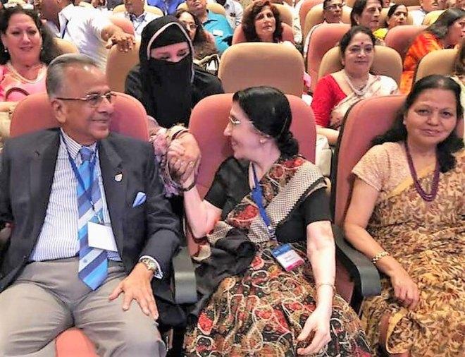 Usha Saboo, seated between PRIP Saboo and Manju Das, greets a Rotarian's spouse.