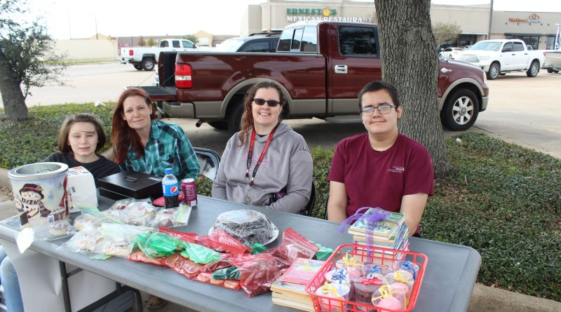 (From Left) Dylan Bunn, Cortni Breman, Kim Avilez and Robert Avilez sat in the Tractor Supply parking lot Sunday raising funds for the Interact Club and accepting new and used books for Books for the World Project. Photo: April Towery, Sealy News