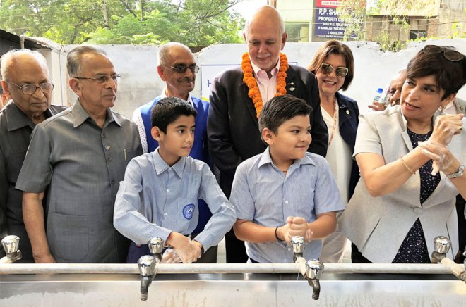 President Rassin, Esther and PRIP Rajendra Saboo get a demonstration on the right handwashing technique.
