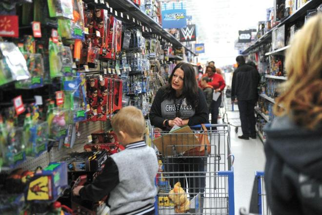 A member of the Morristown AM Rotary Club checks out action figures with a young shopper Tuesday at Walmart.