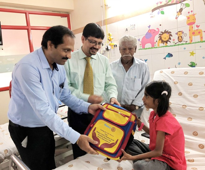 Club President R Saravanan presents a Diwali gift to a child patient.