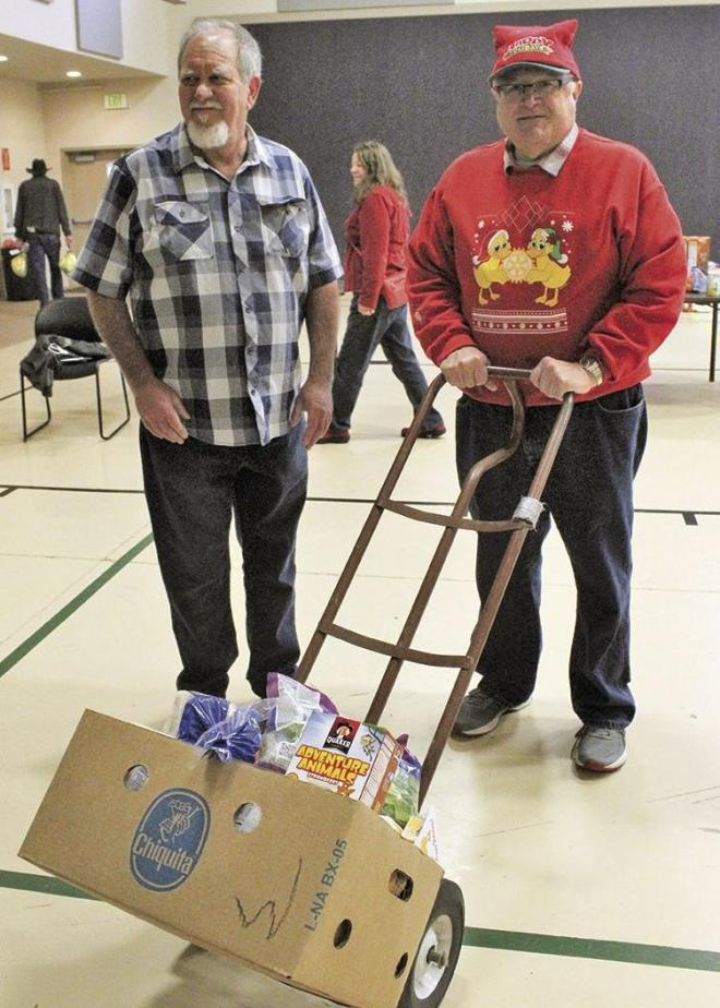 Rotarians Bill Kmet and David Duskin take baskets out to be loaded into cars for delivery.