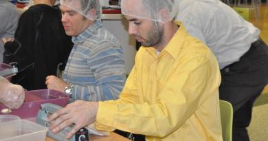 A group of volunteers help package food during a previous Rotary Club event. Photo: The News Herald