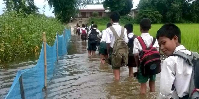 Children trek to school across knee-deep water.