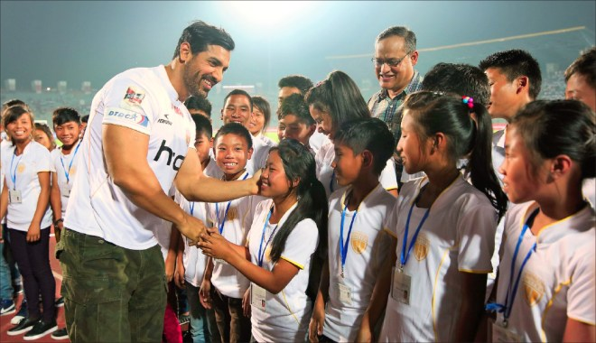 Left: Actor John Abraham greeting the children and Col Rego at a Indian Super League football match in Assam.