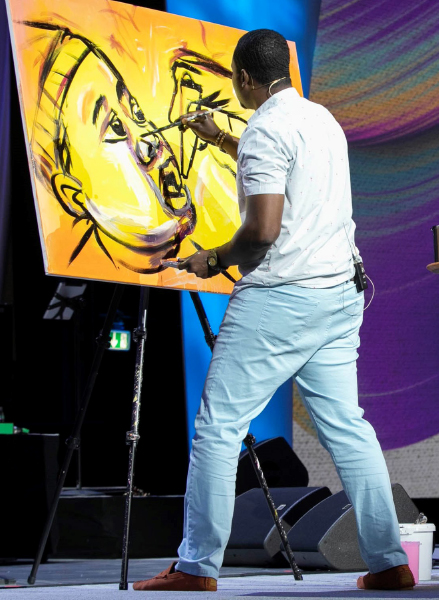 Artist Jamaal Rolle creates a live 'End Polio' painting during the opening ceremony.