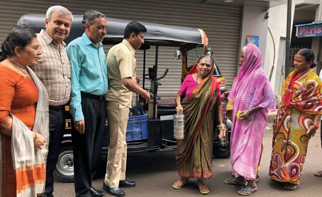 Autorickshaw driver Jagdish Hiremath delivers piping hot meals to women as Rotarians look on.