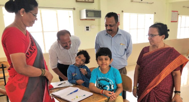 DG Joseph Mathew (centre) and RC Mysore West President Reginald Wesley with the Institute Head Parimala Murthy and children.