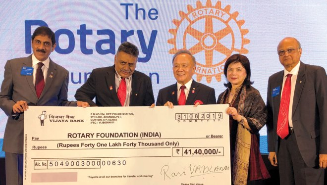 PDG Ravi Vadlamani presenting his cheque to TRF Trustee Chair Gary in the presence of Corinna, TRF Trustee Vahanvaty and EMGA Sam Patibandla (L).