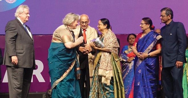 Gay Maloney greets Binota and PRIP Kalyan Banerjee as President Maloney, Vanathy Ravindran, Madhavi and RID Bharat Pandya look on.