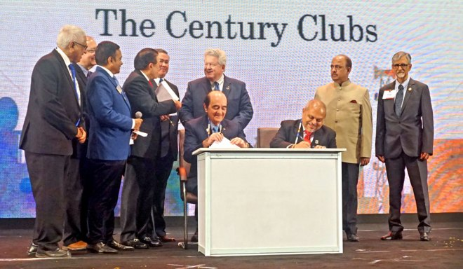 RC Manila President Jackie Rodriguez (seated L) and RC Calcutta President Purnendhu Roy Chowdhury (R) sign an MoA in the presence of RC Calcutta past president Saumen Ray; DG Ajay Agarwal; Nick Locsin, Chairman, International Relations Committee, Manila; RI President Mark Maloney; RIPN Shekhar Mehta and PDG Rajani Mukerji.