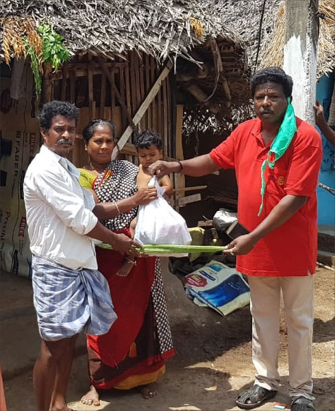 A member of RC Kattumannarkoil Galaxy, RID 2981, giving a grocery bag and vegetables to a tribal family.