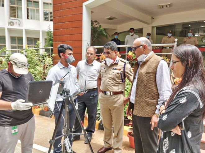 Rtn Harsha M V demonstrating the drone to the Commissioner of Police Bhasker Rao in the presence of RID 3190 Lt Governor V G Kiran Kumar (second from R).