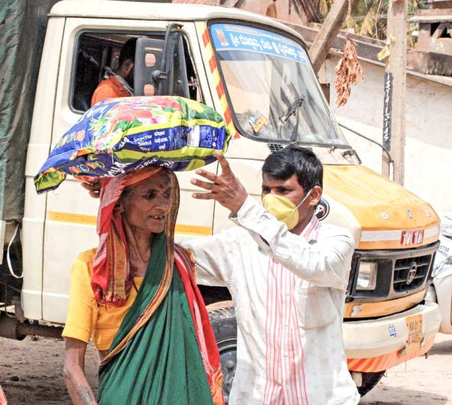A beneficiary being helped to carry her ration kit given by RC Bangalore West.