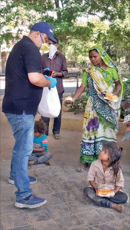 A member of RC Baroda Metro distributing meal packets to a family.