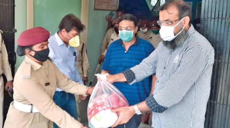 A member of RC Valsad giving protective gear to a police personnel.