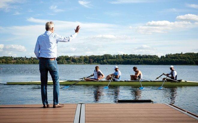 President Knaack greets members of the famed local rowing club as they come back from a training run.
