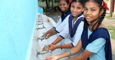 Students washing hands at a handwash station installed under WinS programme.