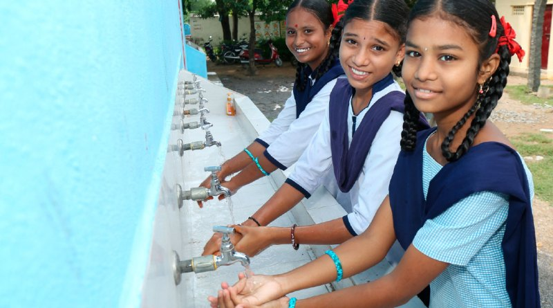 Students washing hands at a handwash station installed under WinS programme.