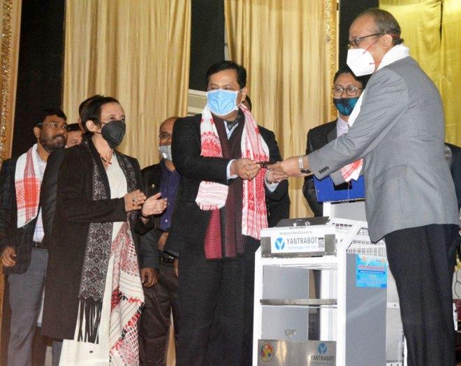 Assam CM Sarbananda Sonowal hands over the robot driving app to AMCH principal Dr Sanjib Kakati in the presence of PDG Kalpana Khound (L).