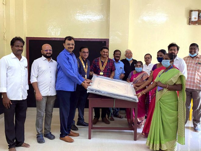 Club President M Nandakumar, Secretary Rajesh Candamourty and project convener DP Raghavan hand over a carrom board to the school authorities.