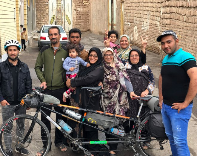 The Iranian family who hosted Naresh Kumar pose with his Tandem cycle.