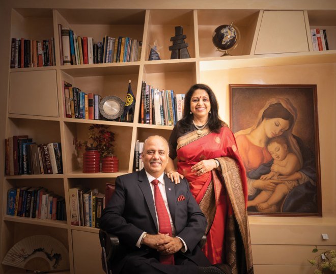"""Shekhar and Rashi Mehta at their home in Kolkata. Rashi painted the picture """"Mother and Child,"""" behind her."""