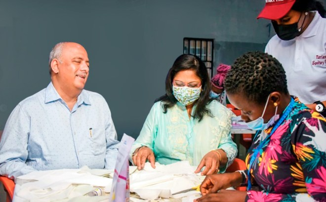 Rashi stitches a reusable sanitary pad in Yaounde, Cameroon, as President Mehta looks on.