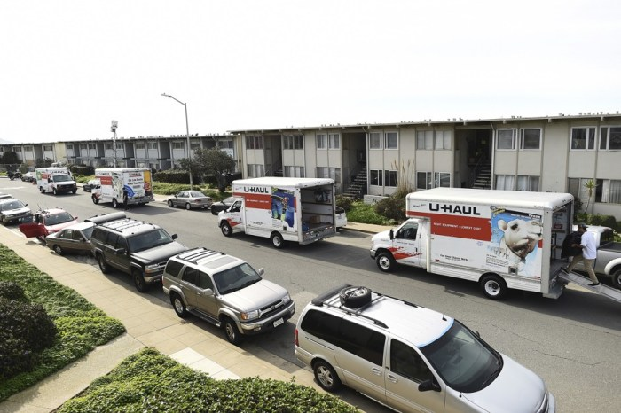 Moving trucks line a streets as residents evacuate from an apartment complex which in danger of collapsing due to El Nino storm erosion in Pacifica