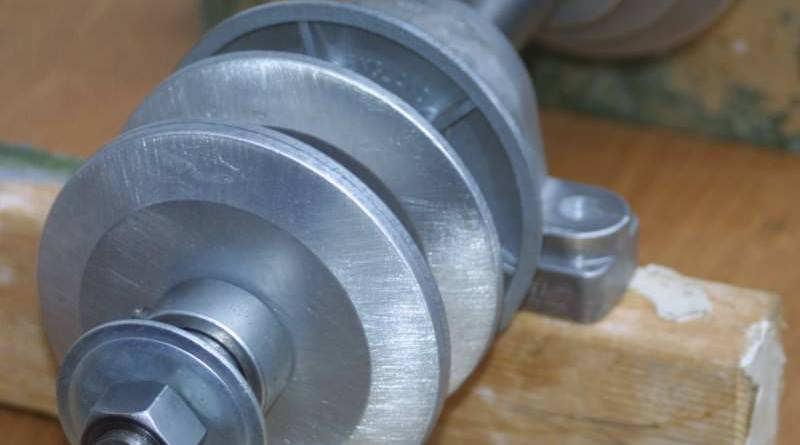 Details view of cabing machine shaft showing threaded end with nut
