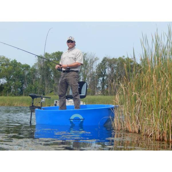 This is a fisherman standing in a blue round boat holding his rod looking for fish