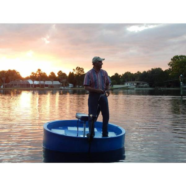 a fisherman smiling on the deck of his round boat, while standing, at sunset.