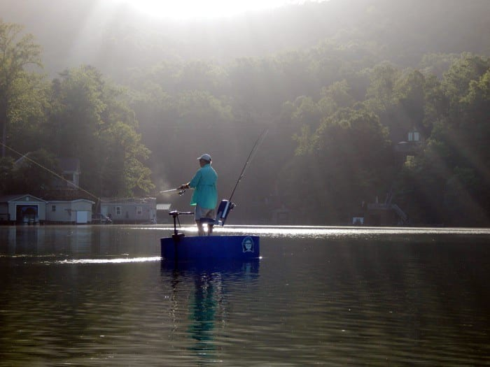 Angler casting a fishing rod from the deck of the round boat