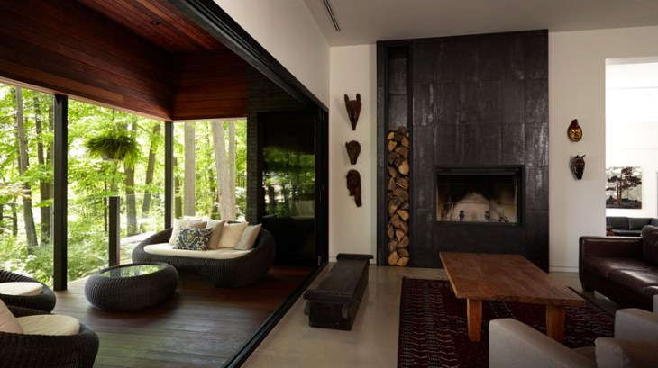 Contemporary home in the forest featuring dark brick exterior 4