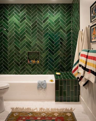 05-a-statement-green-tile-wall-with-a-herringbone-pattern-and-an-additional-green-touch-over-the-bathtub