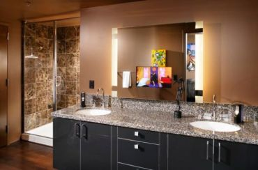 Mirrors-with-side-lighting-and-sober-tones-give-this-masterbath-a-dark-look