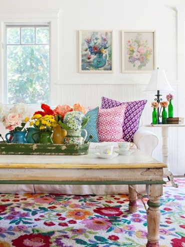 A-bold-summer-living-room-with-floral-artworks-blooms-in-vases-printed-pillows-and-a-colorful-floral-rug-for-a-cheerful-feel