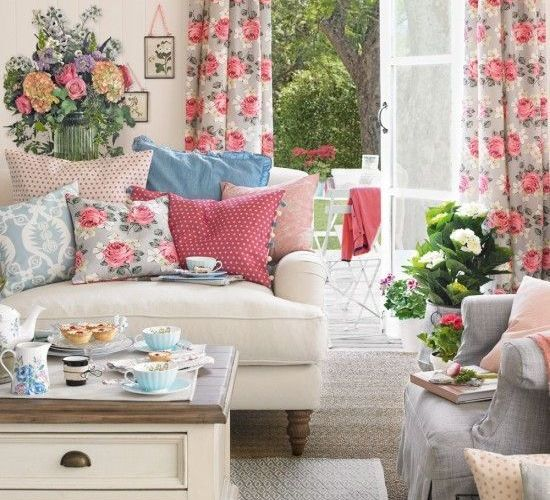 A-vintage-inspired-living-room-with-florla-curtains-printed-pillows-potted-blooms-and-greenery-and-bright-blankets-for-summer