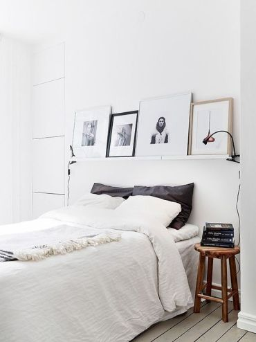 A-white-nordic-bedroom-with-a-ledge-with-artworks-a-comfy-bed-wooden-stools-as-nightstands-and-lamps