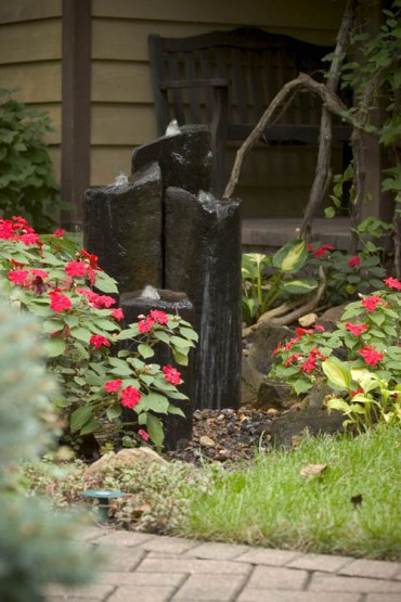 07-a-modern-fountain-of-large-dark-stones-nestled-in-a-bed-of-impatiens-by-the-front-door